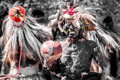 Indigenous Guarani ceremomy Paraguay. Puerto Pollo, Paraguay on August 8, 2015: Indigenous men perform a traditional ceremony using feathers and black body paint Royalty Free Stock Image
