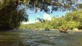 Indigenous kids playing with a river inner tube. In the amazon rainforest stock footage