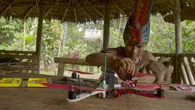 Indigenous man is constructing a drone while being distracted by a monkey