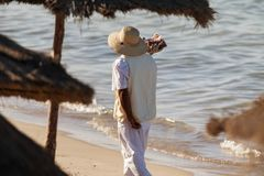 An indigenous man with a hat sells nuts on the beach. Travel to Africa Royalty Free Stock Image