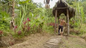 Indigenous man with an injured foot carrying wooden sticks. Walking with difficulty in an amazon village stock video