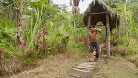Indigenous man with an injured foot carrying wooden sticks slow motion. Indigenous man with an injured foot carrying wooden sticks walking with difficulty in an stock footage