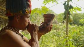 Indigenous Man War Calling. Indigenous Man Playing A Horn Making A War Calling In A Amazonian Village In Ecuador stock video