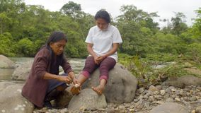 Indigenous old woman applying a bandage to her daughter. In the amazon rainforest stock video footage