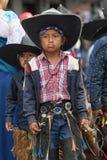 Indigenous quechua boy wearing chaps and sombrero. June 24, 2017 Cotacachi, Ecuador: indigenous quechua children wearing chaps and sombreros participating at the royalty free stock photography