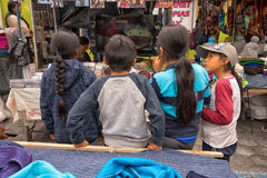 Indigenous quechua children watching television. April 29, 2017 Otavalo, Ecuador: indigenous quechua children watching TV on the street in the Saturday market Stock Images