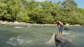 Tribe Man Standing On Rock And Fishing. Indigenous Tribe People Fishing By Amazonian River In Ecuador stock video