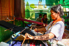 Indigenous woman demonstrating weaving  fabric Royalty Free Stock Photo