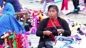 Indigenous woman prepares red yarn to weave. CHIAPAS, MEXICO-CIRCA AUGUST 2018: Indigenous woman prepares red yarn to weave in the public square in San stock footage