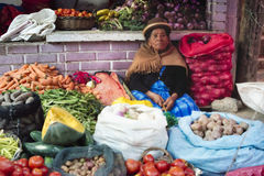 Indigenous woman at the vegetable market using coca leaf on her forehead to relieve headache Royalty Free Stock Images