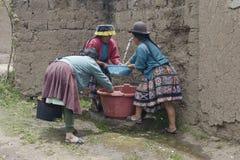 Indigenous women washing chopped raw potatoes Royalty Free Stock Images