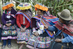 Indigenous women wearing handwoven skirts and ponchos, attending Royalty Free Stock Photo