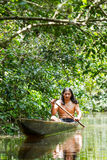 Indigenous Wooden Canoe. Indigenous Adult Man On Typical Wooden Canoe Chopped From A Single Tree Navigating Murky Waters Of Ecuadorian Amazonian Primary Jungle Stock Images