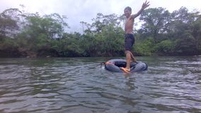 Indigenous young boy trying to balance over a river inner tube. Indigenous young boy playing trying to balance over a river inner tube in the amazon rainforest stock video