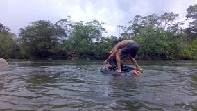 Indigenous Young Boys Trying To Balance Over A River Inner Tube. Indigenous Young Boys Playing Trying To Balance Over A River Inner Tube In The Amazon Rainforest stock footage