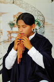 Indigenous young man from Otavalo, Ecuador, playing the rondador Stock Image