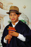 Indigenous young man from Otavalo, Ecuador, playing the rondador Royalty Free Stock Image