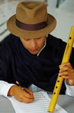 Indigenous young man writing notes to music with quena flute, concept of composition Royalty Free Stock Photo