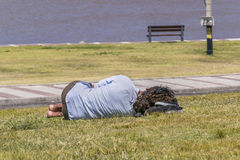 Indigent Slepping at Grass in Park Stock Photo