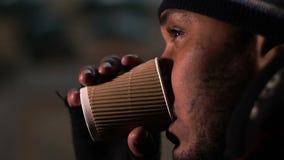 Indigente che beve dalla tazza di carta con gli strappi sul fronte, occhi che splendono con la speranza archivi video