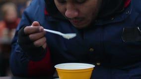Indigente com fome que come o alimento doado por voluntários, evento da caridade para povos pobres filme