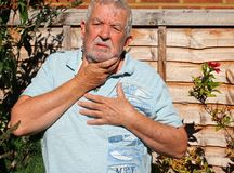 Indigestion. Acid reflux. A senior man holding his chest and throat. He has bad indegestion and acid reflux stock photos