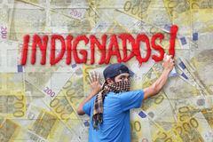 Indignados graffiti euro. Young rioter spraying the Indignados slogan as graffiti on a transparent wall covered with 200 euros banknotes, protesting again the royalty free stock photography