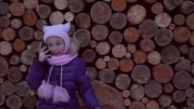 Indignant μικρό κορίτσι που μιλά στο κινητό τηλέφωνο στο ξύλινο υπόβαθρο σύστασης απόθεμα βίντεο