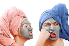An indignant girl beats a guy in the face , mask for skin man and woman, guy with a girl make a mask for the skin together, funny. Indignant girl beats a guy in stock image