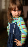 Indignant little girl. Emotional child in striped pullover and denim sarafan Royalty Free Stock Images