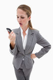 Indignant looking bank employee reading text message Royalty Free Stock Image