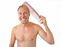 Indignant man hand holding comb on the head Royalty Free Stock Photo