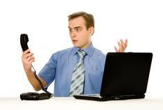 Indignant man working on laptop. Isolated on whi Stock Photo