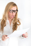 Indignant news. Woman with shocked expression examining a document through her reading glasses Stock Image