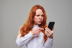 Indignant redhead girl pointing at the screen of teleph stock photo