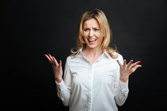 Indignant woman shouting loudly in the black colored studio Stock Photo