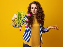 Indignant woman isolated on yellow with wilted flowers. Indignant young woman with long wavy brunette hair isolated on yellow indignant with wilted flowers Royalty Free Stock Photo