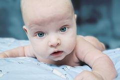 Indigo baby as a space alien. Thoughtful blue-eyed baby is lying on a quilt Royalty Free Stock Photo