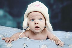 Indigo baby and funny hat. Funny blue-eyed baby wearing cap with ear flaps. Surprised with something Stock Photography
