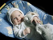 Indigo baby with a toy rabbit. Smiling blue-eyed baby with a toy rabbit in car seat Royalty Free Stock Photo