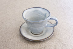 Indigo blue empty coffee cup. On brownish background Stock Images