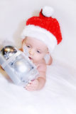 Indigo Christmas baby. Present. Pretty little boy, wearing a Santa's hat, is holding beautiful present. There is some place left for your greetings. Postcard Stock Image