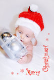 Indigo Christmas baby. Present. Pretty little boy, wearing a Santa's hat, is holding beautiful present. Сhristmas greetings are already there. Ready-to-send Stock Photos
