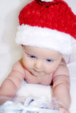 Indigo Christmas baby is taking a present. Pretty little blue-eyed boy is wearing Santa's like hat. He is looking curiously at a beatiful present which is Stock Images
