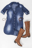 Indigo fabric dress with buttons, belt and brown boots on white background Stock Photography