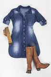 Indigo fabric dress with buttons, belt and brown boots on white background Stock Photo