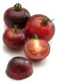 Indigo rose tomatoes. Several Indigo rose tomatoes, one chopped open Stock Photos