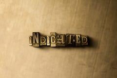 INDIKERAT - närbild av det typsatta ordet för grungy tappning på metallbakgrunden royaltyfria foton