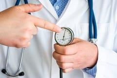 Indikering av högt blodtryckhögt blodtryck i - tålmodigt begreppsfoto Doktor med stetoskopet som pekar vid fingret på nivån av royaltyfria bilder