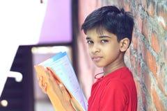 Indio Little Boy con el libro de texto Fotos de archivo